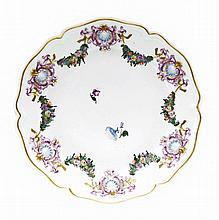 Doccia Assiette à bord contourné à décor en relief rehaussé de polychromie et or de six coquilles dans des cartouches baroques réuni...