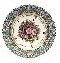 Sèvres Assiette bosselage à godrons à décor polychrome au centre de bouquets de fleurs, l'aile décorée de pétales imbriqués à fond...