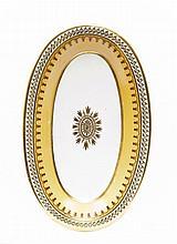 Sèvres Plateau de saucière ovale à décor en or au centre d'une rosace, l'aile décorée de rinceaux en brun sur fond nankin et frise d...