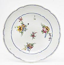 Sèvres Assiette à bouquets et palmes en relief sur l'aile en porcelaine tendre à décor polychrome de bouquets de fleurs et filets...