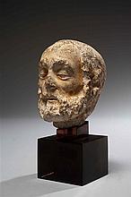 Petite tête de Saint barbu en pierre calcaire sculptée avec dépôts d'argile. Epaisses arcades sourcilières, yeux étirés vers les tem..
