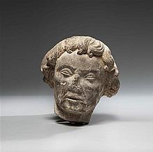 Tête d'homme en pierre calcaire sculptée avec traces de polychromie, arrière arasé. Visage avec yeux en amande aux paupières gonflée..