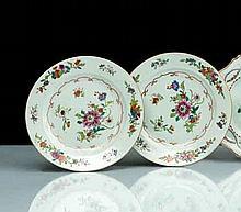 Chine Deux assiettes à décor polychrome des émaux de la famille rose de bouquets de fleurs dans un médaillon et branches fleuries sur l