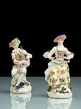 Meissen Paire de statuettes représentant Arlequin et Colombine assis sur un tronc d'arbre, lui vêtu d'un gilet décoré de cartes à jou
