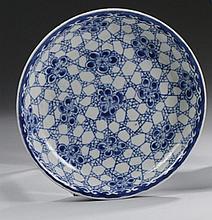 CHINE Époque KANGXI (1662-1722) Coupe en porcelaine décorée en bleu sous couverte de pruniers en fleurs sur fond de miroir brisé. Di...