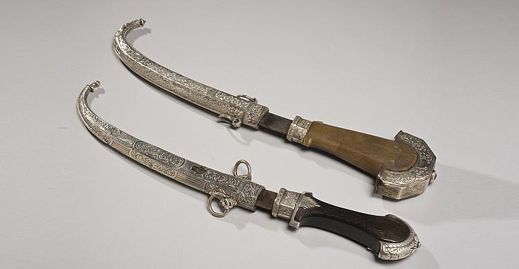 Deux poignards koummiya à lames courbes en acier et poignées en bois terminées en queues de paons