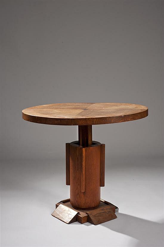 Charles DUDOUYT (1885-1946) Table circulaire en bois, le plateau reposant sur un fût central à ellipses, la base carrée se terminant...