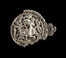 Elément décoratif en argent repoussé et gravé de forme circulaire à décor d'un cervidé couché, la tête retournée dans un entourage d..
