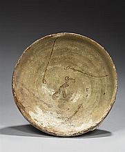 Coupe sur piédouche en céramique argileuse à glaçure vert pâle avec décor incisé en sgraffito élaboré d'un oiseau au centre et de qu...
