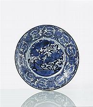 Japon (Arita) Grand plat rond à décor en bleu sous couverte de pivoines en fleur sur une terrasse, l'aileRdécorée de larges rinceaux d