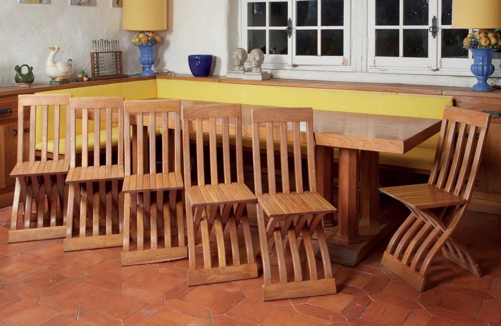 Tavola in legno chiaro sostenuta da colonne lignee ottogonali
