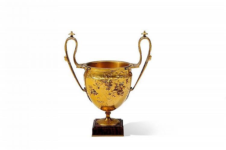 Vase à piédouche en bronze ciselé doré à deux anses ajourées, à décor en relief de branches fleuries. Signé sur lapanse « Maison F...