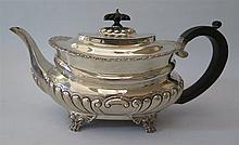 A George V Silver Teapot standing on lion paw feet with gadrooned waist and