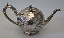 A Georgian Silver Teapot with embossed foliate scroll decoration, London 18