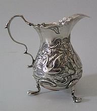 A George III Silver Cream Jug with repoussé decoration of swan and hair cou
