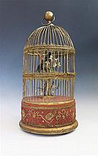 A Large Clockwork Automaton Singing Bird in a gilt cage with gold thread em