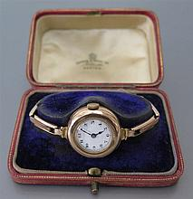 A Ladies 9ct Gold Cased Wristwatch with enamel dial 9ct gold bracelet, the