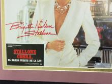 Lot 158: BRIGITTE NIELSEN STALLONE COLOR SIGNED SPANISH MOVIE POSTER
