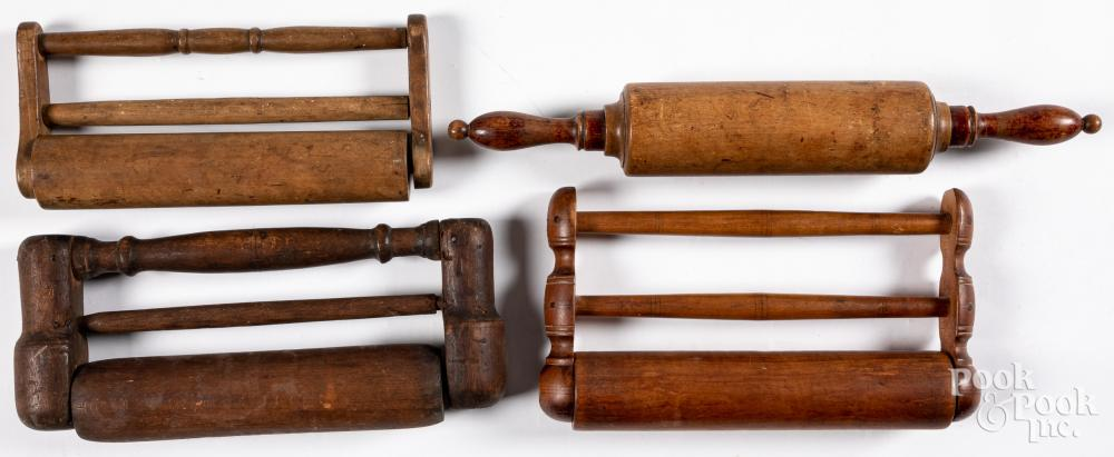 Four antique wood rolling pins.