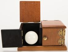 """Billiard Ball Box. Los Angeles: F.G. Thayer, ca. 1925. Handsome wooden box, similar to a traditional die box, but performed with a white billiard ball. The ball vanishes from the cabinet and reappears elsewhere. Gimmick for stealing the ball from cabinet and """"double door"""" designed differently than traditional boxes. 7 x 3 ¾ x 3 ¾"""". Light external wear; good. Scarce."""