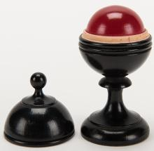 """Billiard Ball Vase. Los Angeles: F.G. Thayer, ca. 1920. A solid red ball removed from a hardwood vase vanishes, then reappears inside. Finely turned from rock hard maple by Floyd Thayer himself. Black lacquer. Uncommon smaller size; ball 1 ½"""" diameter, vase 4 1/8"""" high. Very good."""