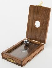 Cabala. Asuza: Owen Magic Supreme, ca. 1995. A steel ball bearing penetrates a sheet of glass locked in a handsome hardwood cabinet held in the magician's hands. Hallmarked. Fine.