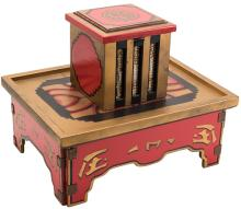"""Chest of Chu Chin Chow. Los Angeles: F.G. Thayer, ca. 1928. Rice is poured into a brightly decorated box on a wooden tray and stand. Grains can be seen through windows in the box, then vanish visibly, or suddenly transform into other objects. Folding tabletop model, brightly decorated, outfitted with leather hinges. Multiple mechanical principles built in. Stand 16 ¼ x 12 ¼ x 6 ¾"""". Scarce."""