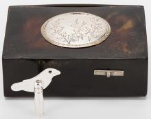 Tortoiseshell Singing Bird Box. Germany: Karl Griesbaum (attributed to), ca. 1905. Mechanical singing bird box with polished tortoiseshell case. Silver engraved lid depicts flowers and a bird in flight. Articulated wings and beak. Hinged key compartment at rear. Bird sings and moves for approximately sixteen seconds before disappearing back inside the box. With later key. 3 ¾ x 2 ½ x 1 ¼?. Good working condition. Video on request.