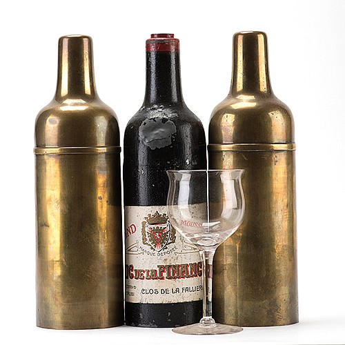 Passe Passe Bottles. French, ca. 1890. A claret glass and a bottle change places repeatedly when placed underneath respective turned brass covers. An early model, with covers modeled after the shape of the bottle. 10 _î high. Wear to finish of