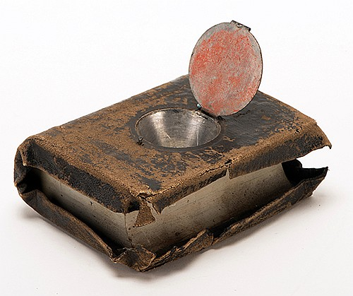 Production Bible. Circa 1900. Contoured wooden block covered in leather, resembling a pocket Bible, with a metal cover over an inverted cone-shaped opening that may be secretly released by a lever on the opposite side. 5 x 4 x 2î. Age-consistent
