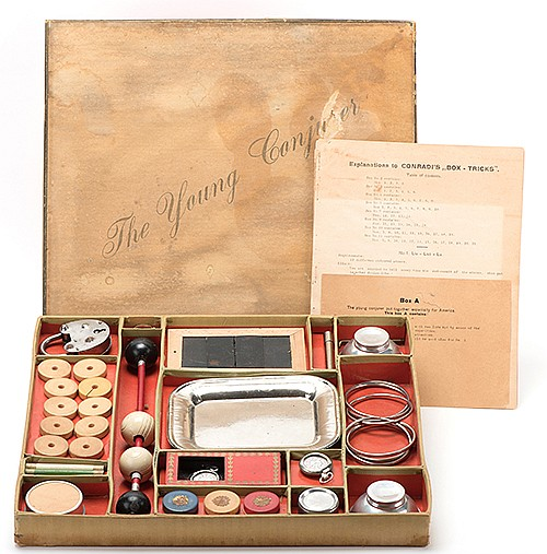 The Young Conjurer Magic Set. Hamburg: F.W. Conradi, ca. 1925. Large and elaborate magic set includes metal coin tray, Linking Rings, Rice Bowls, Coin Box, Vanishing Cigarette Tube, trick padlock, and a Creative Silks-type silk production. Other