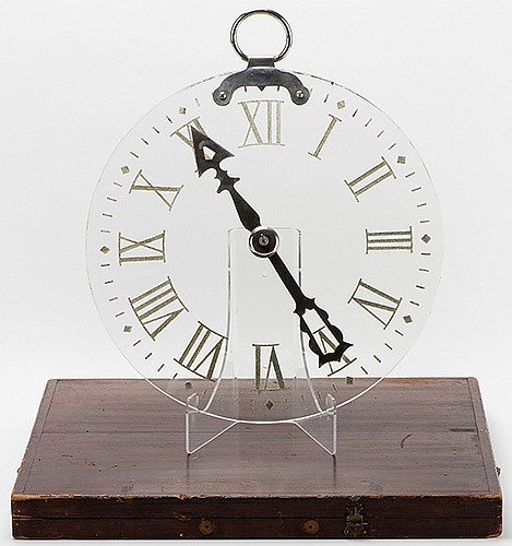 Spirit Clock Dial. New York: Martinka & Co., ca. 1900. The hand on a crystal clear clock is spun, and stops at the number chosen by the magician or one of his spectators. Glass dial 14 _î diameter. With original fitted wooden packing case, pointer
