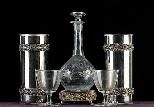 Wine and Water Separation. Chicago: August Roterberg, ca. 1910. Two metal canisters decorated with floral pattered accents made of metal, two claret glasses, and a claw-footed metal stand, and a glass decanter make up the apparatus. Wine and water