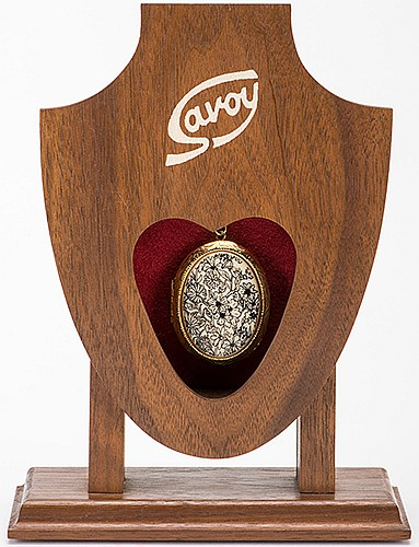 The Savoy. Huntington Beach: Magikraft Studios, 1993. A wooden stand allows the magician to switch one metal locket for a duplicate in the action of pulling the first locket free. With original instruction booklet by Eric Lewis. Fine.