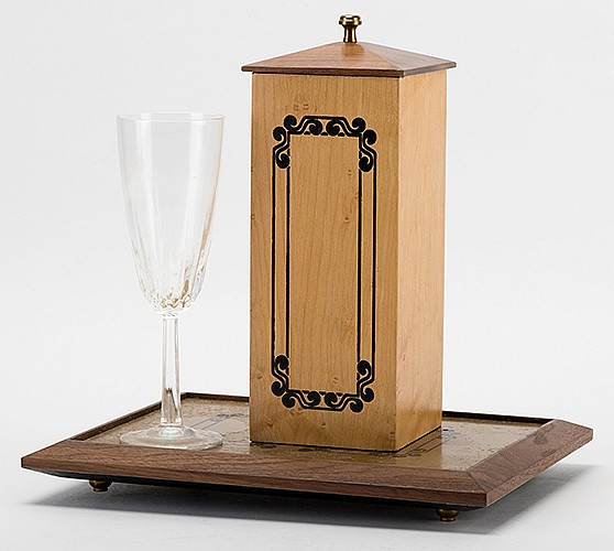 Self-Priming (Automatic) Siphon. Riverside: Magikraft Studios (Martin Lewis), ca. 1995. A champagne flute isolated on a tray is filled with liquid and covered with a tube. Despite no contact between the magician and the glass, the liquid vanishes.