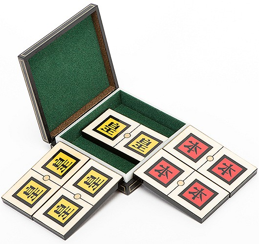 Dizzy Dominos (Chinese). Holland: Eddy Taytelbaum, 1970s. Five handmade reverse-painted plastic laminated domino tiles, three in yellow, two in red, which transpose from place to place. With felt-lined wooden carrying case. Fine.