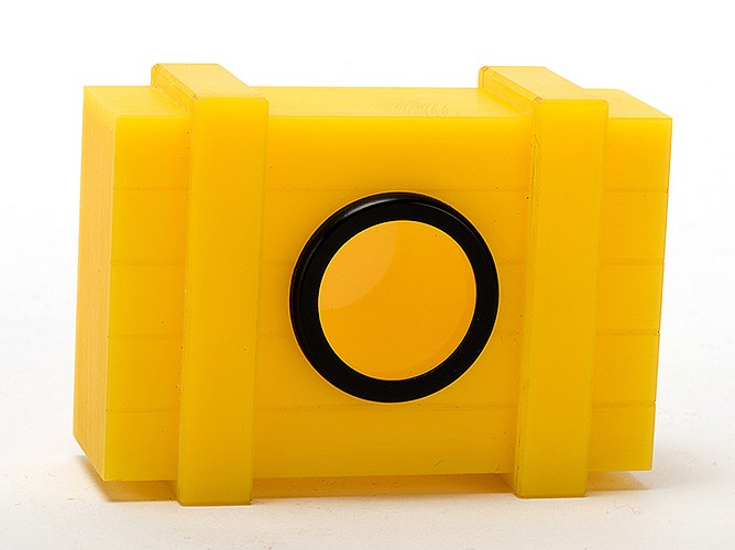 Puzzle Box. Holland: Eddy Taytelbaum, ca. 1970s. Miniature hard plastic yellow crate with a small glass window. In the magicianÍs hands rings or coins appear in the crate, but others cannot open the device. 3 x 2 _ x 1î. Fine.