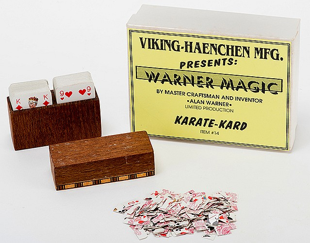 Karate Kard. Middlesex: Alan Warner, ca. 1990. A chosen card from a patience-sized pack of cards is placed into a box. When the box is opened, all the cards have been sliced into tiny pieces _ except for the selection. Teakwood construction. With