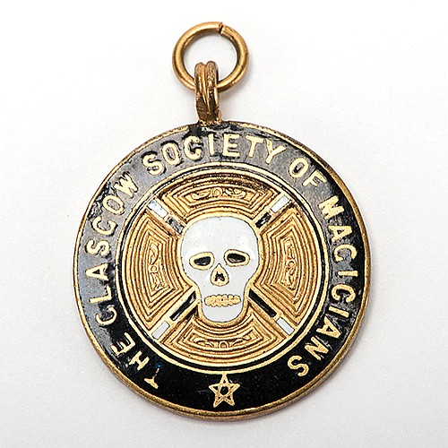 RaymondÍs Glasgow Society of Magicians Badge. London: E. Simons, ca. 1918. Gold-filled enamel pendant owned by The Great Raymond, with central logo of skull and wands, engraved on the verso by the manufacturer. Approx. 1î diam. Owned by The Great
