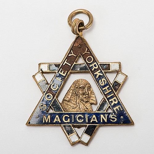 RaymondÍs Society of Yorkshire Magicians Presidential Pendant. Circa 1910s. Gold-plated enamel pendant engraved on the verso ñPresident/ Great Raymond.î Approx. 1 _î diam. Losses to enamel border at top.
