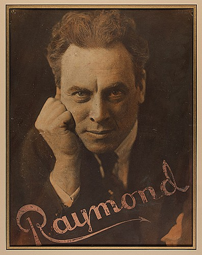 Raymond, Maurice F. (Morris Raymond Saunders). Studio Portrait of Raymond. N.p., ca. 1930s. Handsome large studio portrait of the magician resting his head on his hand, printed with reddish hues, with his well-known name logo stamped in light pink
