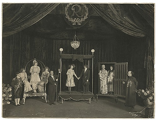 Raymond, Maurice F. (Morris Raymond Saunders). Stage Illusion Lobby Photo. Chicago: Kaufmann, Weiner & Fabry Co., ca. 1915. Silver gelatin print depicting Raymond on stage with ten assistants including men in exaggerated Oriental costumes and two
