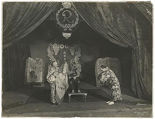 Raymond, Maurice F. (Morris Raymond Saunders). Stage Illusion Lobby Photo. Chicago: Kaufmann, Weiner & Fabry Co., ca. 1915. Silver gelatin print depicting men dressed in exaggerated Oriental costumes and another man kneeling on a short table. 14 x 10