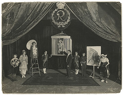 Raymond, Maurice F. (Morris Raymond Saunders). Stage Illusion Lobby Photo. Chicago: Kaufmann, Weiner & Fabry Co., ca. 1915. Silver gelatin print depicting Raymond at center stage, holding the hand of an assistant in a suspended cage, while others