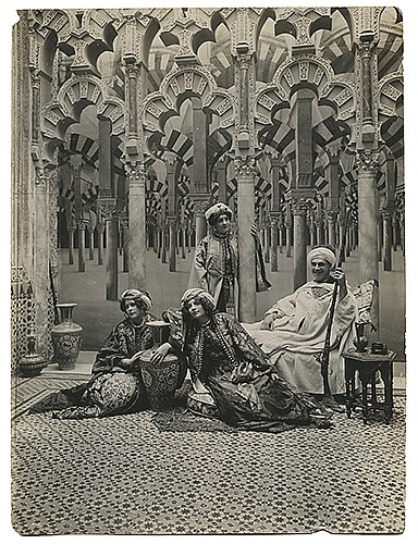 Raymond, Maurice F. (Morris Raymond Saunders). Portrait of Raymond with Assistants. Circa 1920. Silver gelatin print, a striking image of Raymond with three assistants, the tableau and garb evocative of the Middle Eastern themes the performer