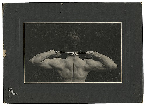 Raymond, Maurice F. (Morris Raymond Saunders). Portrait of Raymond Shackled. San Francisco: Bushnell, ca. 1910. Beefcake-style portrait in which Raymond is shown shackled at the neck and wrists. On photographerÍs mount. 8 x 11î. Scuffs, edge wear