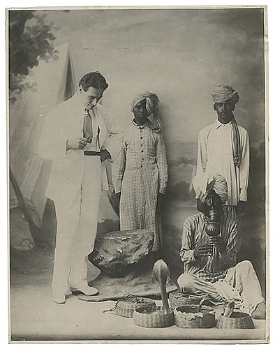 Raymond, Maurice F. (Morris Raymond Saunders). Three Photographs of Raymond with Snake Charmers. Circa 1930s. Raymond, in white suit, observes as young men charm artificial snakes from their baskets using wood instruments and a drum. 9 _ x 8î.