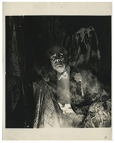 Raymond, Maurice F. (Morris Raymond Saunders). Dramatic Studio Portrait of Raymond. N.p., ca. 1940s. The magician stares intensely at the viewer in a room draped with silks, as wisps of smoke and bright lighting from below lend the scene a haunted