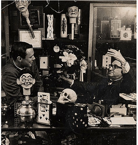 Flosso, Al (Albert Levinson). Portrait in Magic Shop. New York, ca. 1965. Large gelatin silver print taken at the Coney Island FakirÍs famous magic shop on 34th Street in Manhattan, depicting Flosso gesturing toward a young man leaning against the