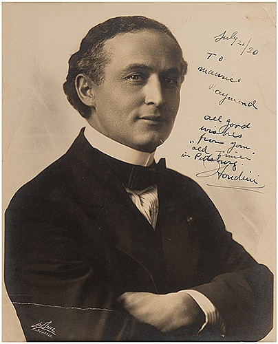 Houdini, Harry (Ehrich Weiss). Portrait of Houdini Inscribed and Signed to Raymond. Seattle: LaPine Studio, ca. 1916. Silver gelatin portrait of Houdini in formal attire, arms crossed, staring into the camera. Inscribed and signed in black ink,